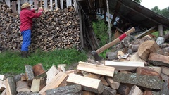 Tired worker man put wood in ordered row in country woodshed. 4K Stock Footage