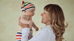 Loving mother playing with her baby. Dressed baby in striped shorts and cap Stock Footage