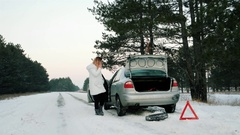 Car broke, need to put the spare tire, woman talking on a cell phone, calls for Stock Footage