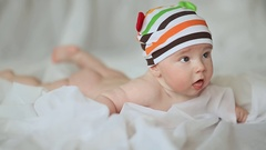 Funny four month old baby lying on his stomach and smiling Stock Footage