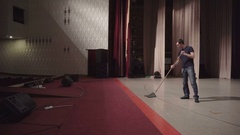 Man washes theater stage using a mop Stock Footage