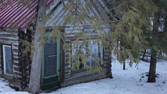 Man walks around his winter cabin in woods towards camera Stock Footage