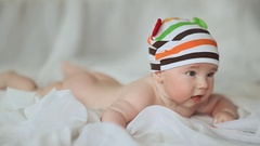 Funny four month old baby lying on his stomach and smiling. Slow motion shooting Stock Footage