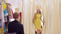 Attractive adult girl with smile shows yellow dress to the guy in dressing room Stock Footage