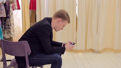 Young man looking at smartphone while his girl changes clothes in fitting room Stock Footage