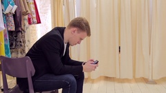 Young man laughed looking at smartphone while his girl changes clothes in stote Stock Footage