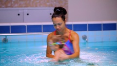 Young mother recreates her liitle son in the swimming pool Stock Footage
