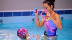 Beautiful mother recreates with her little daughter in the swimming pool Stock Footage