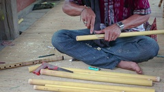 Balinese craftsman hand carves flutes from bamboo tubes in Indonesia Stock Footage