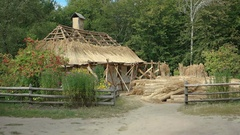 Old, thatched roof house being recovered with fresh thatch Stock Footage