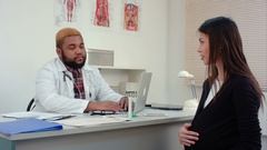 Pregnant woman visiting young smiling male doctor Stock Footage