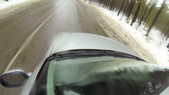 Camera mounted on a car when moving on winter road in forest. It goes sleet Stock Footage