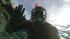 The man in the mask under the water waving at the camera Stock Footage
