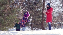 Flying snow clumps between mother and daughter. family fun winter games in the Stock Footage