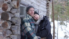 Bearded man happy holding his girlfriend outside cabin in woods Stock Footage