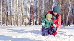 The winter games in snowy urban Park. Young mother playing with her little son Stock Footage