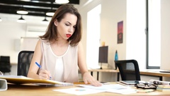 Woman looking for missing document on her table in office Stock Footage