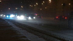 Cars on the city road in a snowstorm at night. Stock Footage