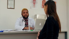 Pregnant woman visiting young smiling Afroamerican male doctor Stock Footage