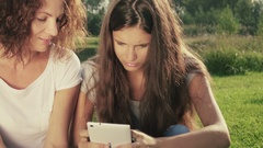 Mother and daughter outdoors on grass watch and discuss something on smartphone. Stock Footage