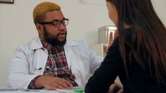 Afroamerican doctor prescribing pills to female patient and explaining dosage Stock Footage