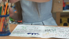 Child draws the pictures in the copybook indoors Stock Footage