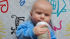 Portrait of infant baby tries to eat from a bottle in bed by himself. Healthy Stock Footage