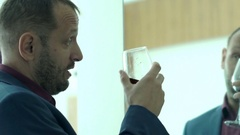 Drunk businessman drinking wine and talking to mirror at home Stock Footage