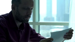 Young businessman reading, analyzing documents in the office Stock Footage