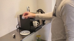 The young man puts capsule coffee in the coffee machine. Stock Footage