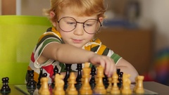 Little genius with glasses fascinated by the game of chess. Stock Footage