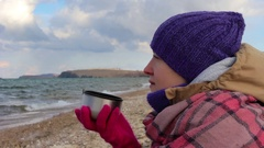 Girl sits on the shore of the sea and drinks a hot tea. Waves, beautiful scenery Stock Footage