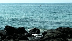 Canoe On Tropical Sea Water Surging Up On Black Lava Rock Shore Stock Footage