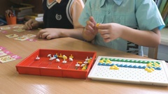 Two boys collect figures using colored chips Stock Footage