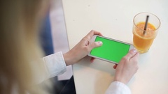 Young woman browsing mobile phone with a green screen at the coffee shop Stock Footage
