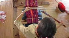 Woman weaves intricate patterns on loom as baby lies alongside Stock Footage