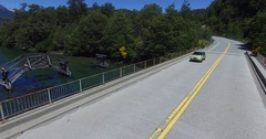 Aerial drone scene of route and old wooden broken bridge. Car passing by. Stock Footage