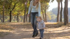 Cute 1 year old baby boy holding mothers hand and walking at autumn park Stock Footage