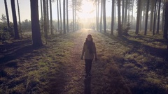 Into the woods - girl walking into winter forest, sun behind her Stock Footage