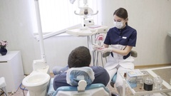 Dentist young woman making procedures to men patient at dental office. Concept Stock Footage