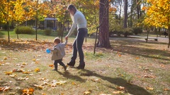 Happy mother holding her baby son and walking at autumn park Stock Footage