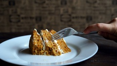 Cutting piece of carrot cake with fork. Man eating dessert cake. Slice of cake Stock Footage