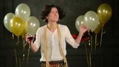 Joyous Party Girl Enjoying Dance among Confetti on Black Background with Stock Footage