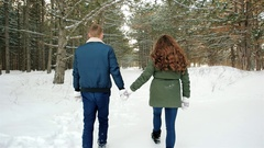 Winter walk, Beautiful guy and the girl go on a snowy road through the trees Stock Footage