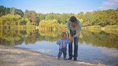 Beautiful young mother walking with her baby son by the lake at park Stock Footage