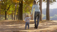 Adorable baby boy walking with mother in autumn park at sunny day Stock Footage