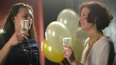 Two Smiling Ladies are Clinking Glasses with Champagne During a Party and Stock Footage