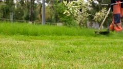 City gardening activity. Worker in uniform mowing lawn with trimmer. Urban scene Stock Footage