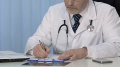 Professional physician writing treatment prescription in patient medical record Stock Footage