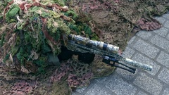 Army sniper wearing disguise camouflage suit at military show. 4K clip Stock Footage